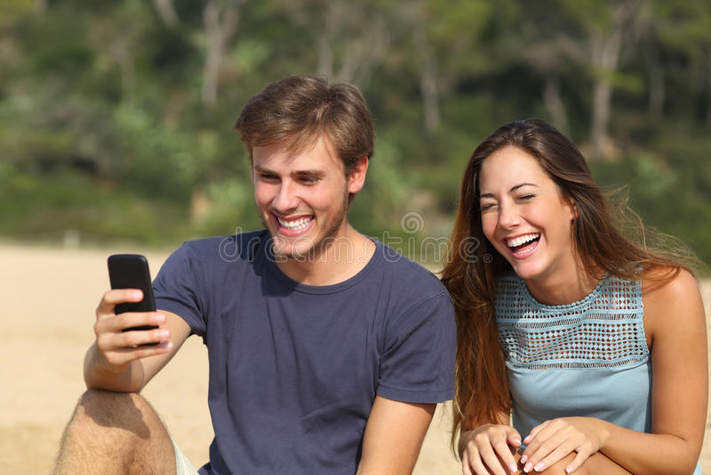 Смешной человек и женщина смеясь над наблюдающ умный телефон стоковые фото