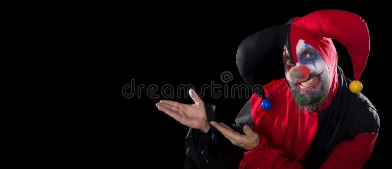 Смешной шут показывая к copyspace, концепции хеллоуину и ужасу стоковое фото rf