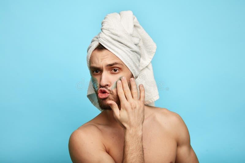 Смешной эмоциональный парень поя песню пока прикладывающ лицевую сливк стоковая фотография rf