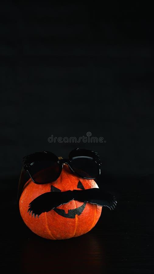 смешной halloween Тыква в черных солнечных очках и усике на черной предпосылке Мальчик отца человека тыквы Концепция хеллоуина с стоковое фото rf