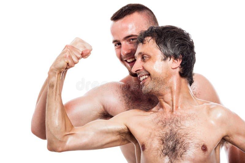 Смешные без рубашки люди сравнивают бицепсы стоковое фото rf