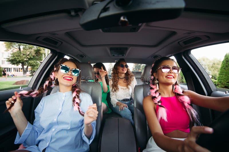 Смешные девушки с солнечными очками имеют потеху, конек в дорогом автомобиле Свертывать и петь в автомобиле в их родном городе на стоковое изображение rf