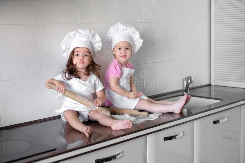 Смешные дети подготавливают тесто, пекут печенья в кухне, счастливую семью стоковая фотография
