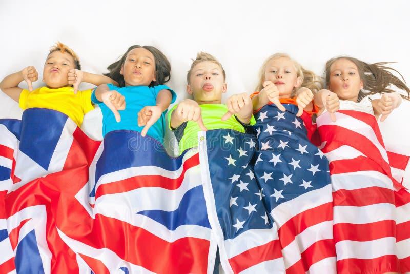 Смешные дети держа флаг Великобританию и американский национальный флаг стоковые изображения rf