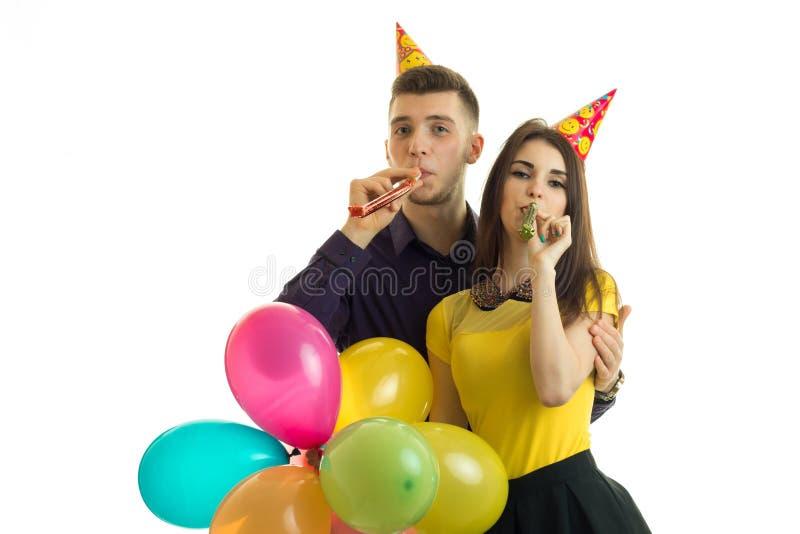 Смешные молодые пары празднуя день рождения с конусами на их головах держат покрашенные шарики и дуют рожки стоковая фотография