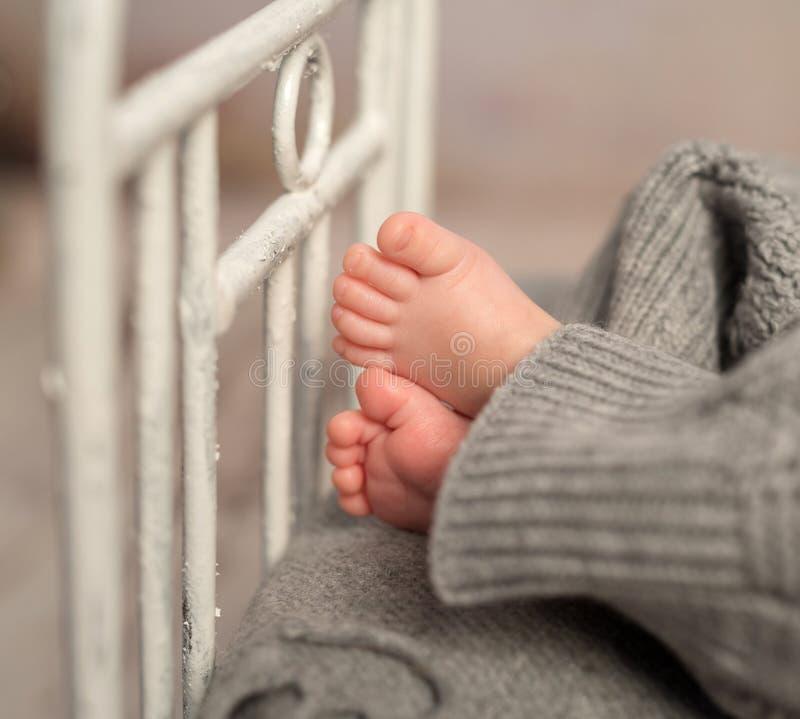 Смешные ноги младенца из серых брюк на кроватке стоковая фотография