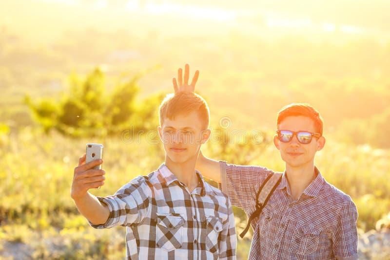 Смешные парни друзей сфотографированы на selfie телефона на солнечный день стоковая фотография