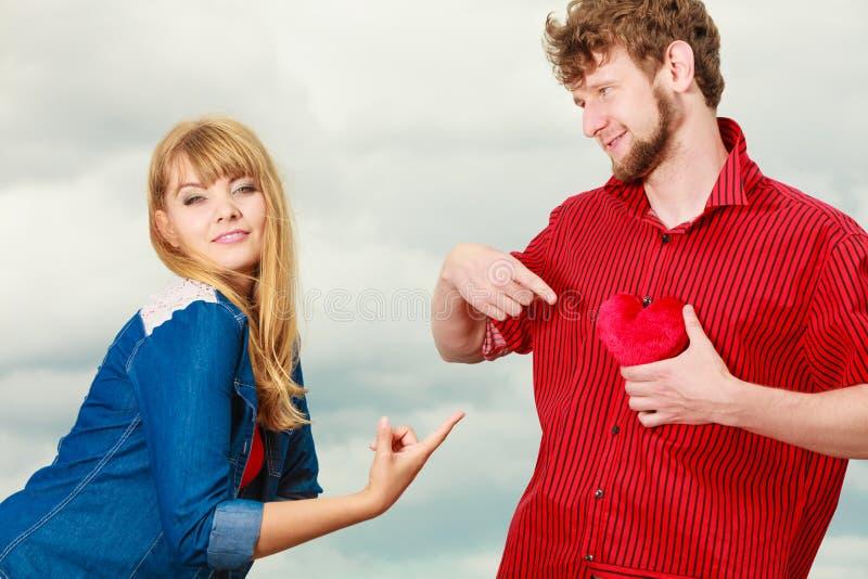 Смешные пары в влюбленности играя с красным сердцем внешним стоковая фотография rf