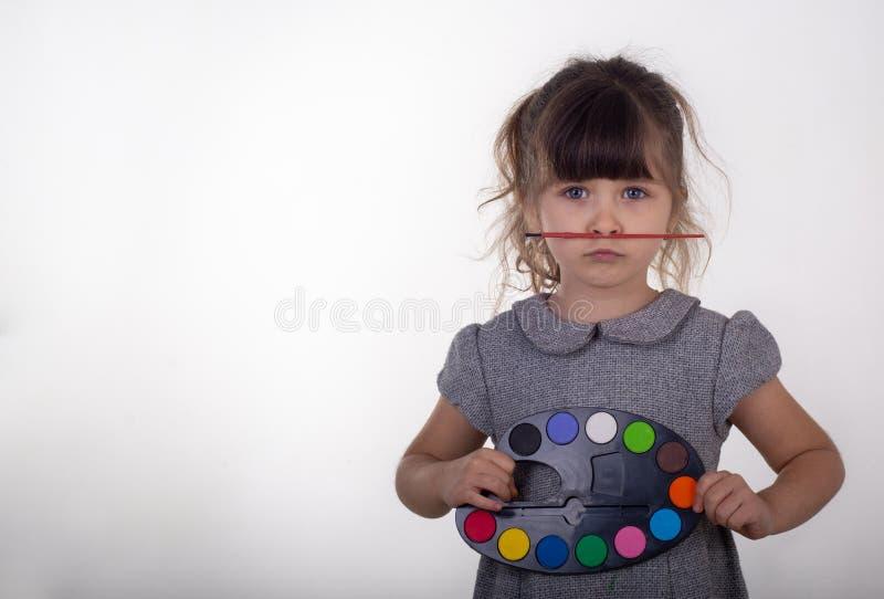 Смешные 5 старой лет палитры удерживания ребенка красок для рисовать и paintbrush стоковое фото