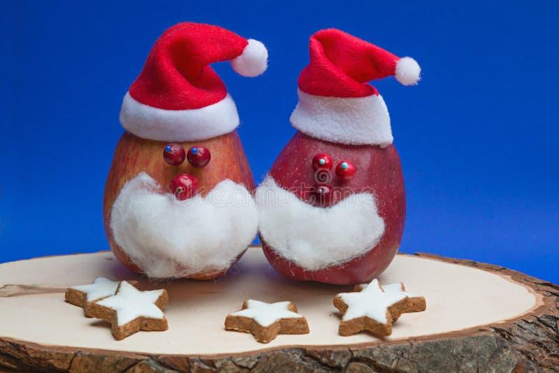Смешные яблоки Санта Клауса, на деревянной доске с печеньями рождества стоковые изображения