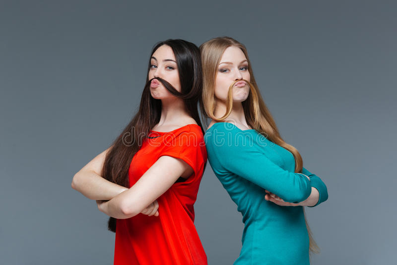 2 смешных женщины делая усик с их волосами стоковые изображения