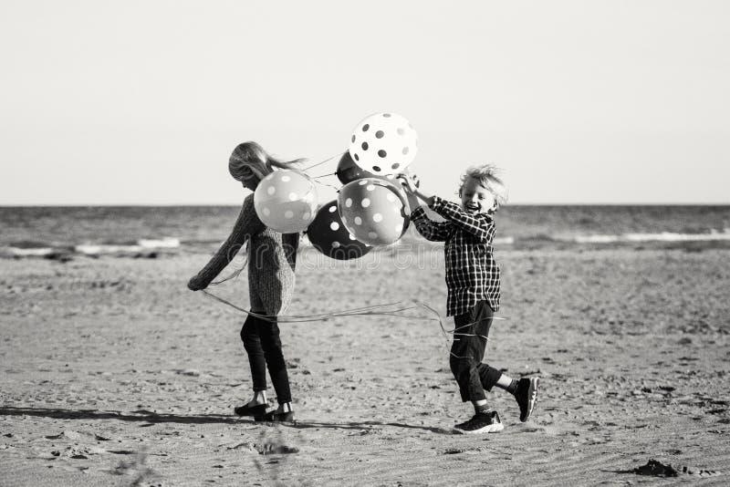 2 смешных кавказских дет ягнятся при пук воздушных шаров играя бежать на пляже стоковое фото