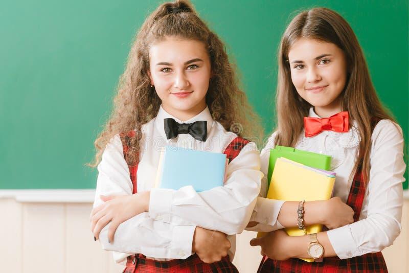 2 смешных школьницы в школьной форме стоят с книгами на предпосылке школьного правления стоковые изображения