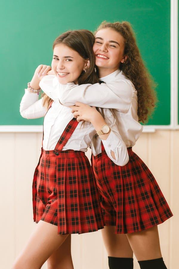 2 смешных школьницы в школьной форме стоят с книгами на предпосылке школьного правления стоковое изображение rf