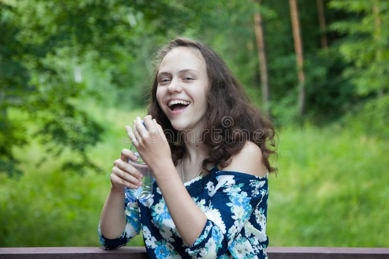 Смеющся, жизнерадостный счастливый девочка-подросток в природе, в руках чистой питьевой воды в бутылке стоковое фото rf