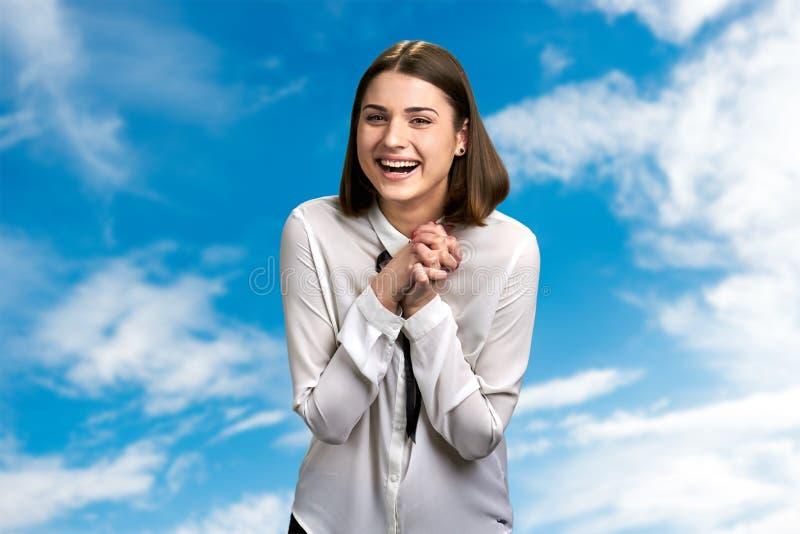 Смеясь женщина на предпосылке облачного неба стоковые изображения