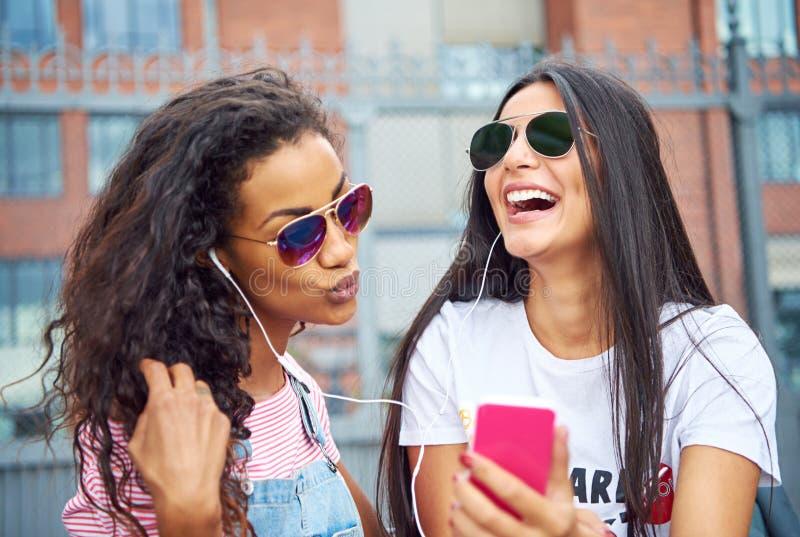 Смеясь молодые друзья усмехаясь и принимая outsi selfies совместно стоковая фотография