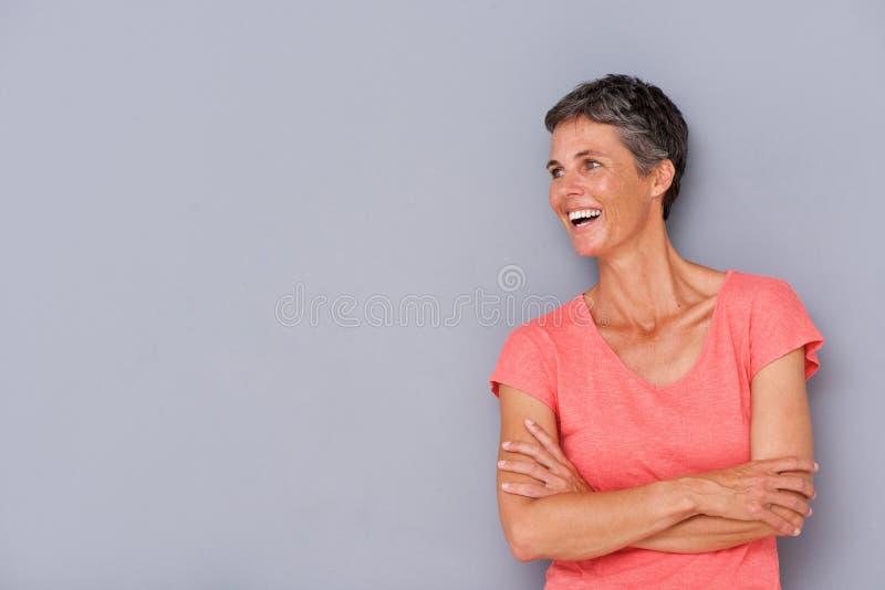 Смеясь над более старая женщина против серой стены стоковые фотографии rf