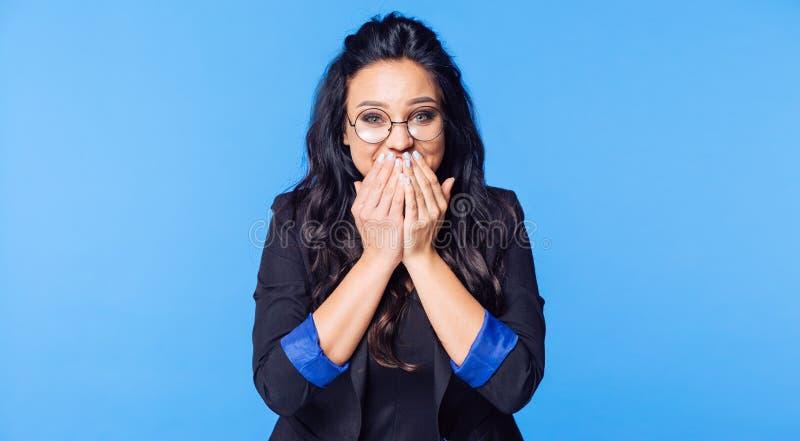 Смеясь над девушка в выставках черных куртки закрывает его рот с его руками стоковое изображение rf