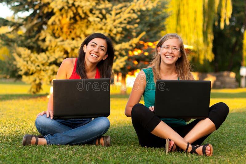 Смеясь над девушки outdoors с компьтер-книжкой стоковые фото