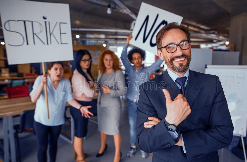 Смеясь над директор показывая большой палец руки вверх, поразительные работники на фоне стоковые фотографии rf