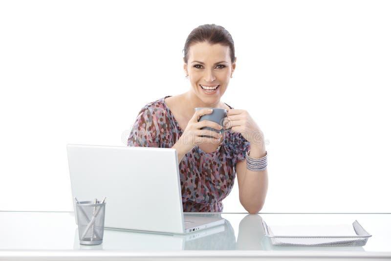 Смеясь над женщина на столе офиса стоковая фотография rf