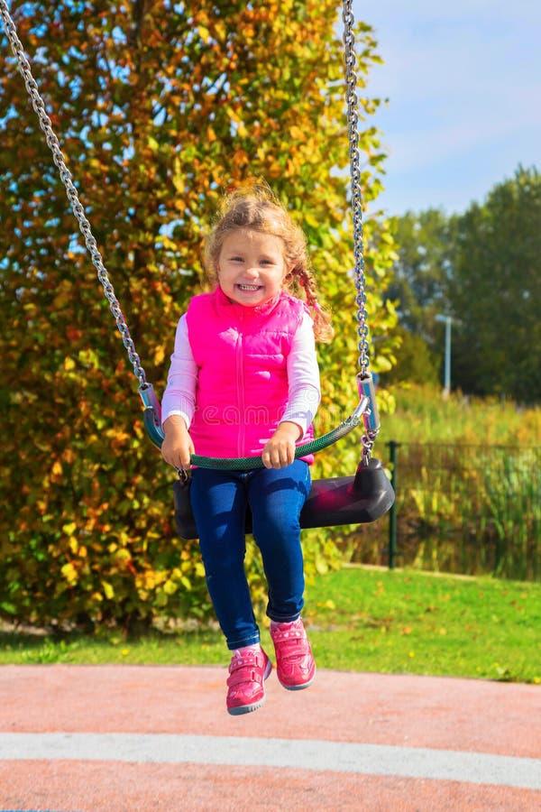 Смеясь над маленькая девочка отбрасывая на качании стоковое фото