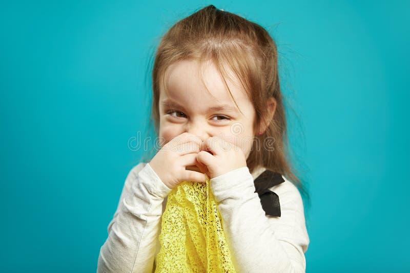 Смеясь над маленькая девочка покрывает ее сторону с руками, улыбками кокетливо и застенчиво, выражает замешательство и застенчиво стоковое фото rf