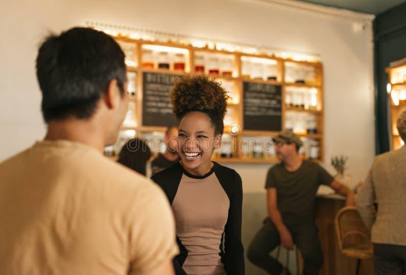 Смеясь над молодая женщина разговаривая с ее другом в баре стоковое изображение