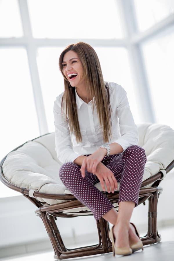 Смеясь над молодая женщина сидя в удобном стуле стоковое фото