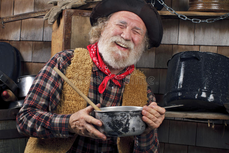 Смеясь над старый кашевар ковбоя держит кастрюльку стоковые фото