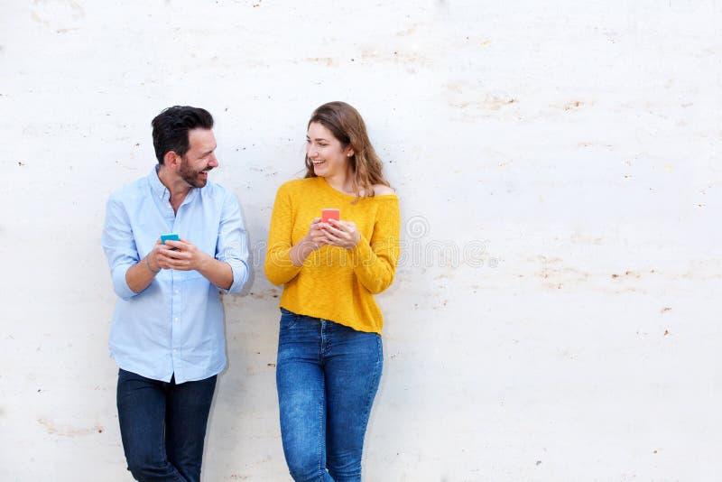 Смеясь над стена пар готовя белая держа мобильные телефоны стоковое фото