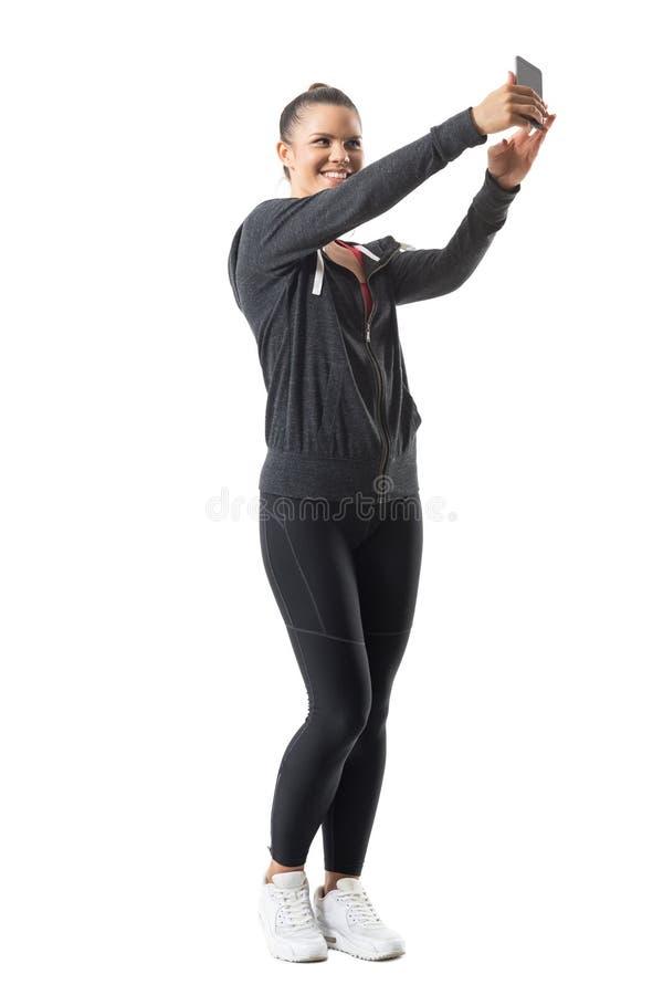 Смеясь над счастливая молодая спортсменка фотографируя при мобильный телефон смотря мобильный телефон стоковая фотография