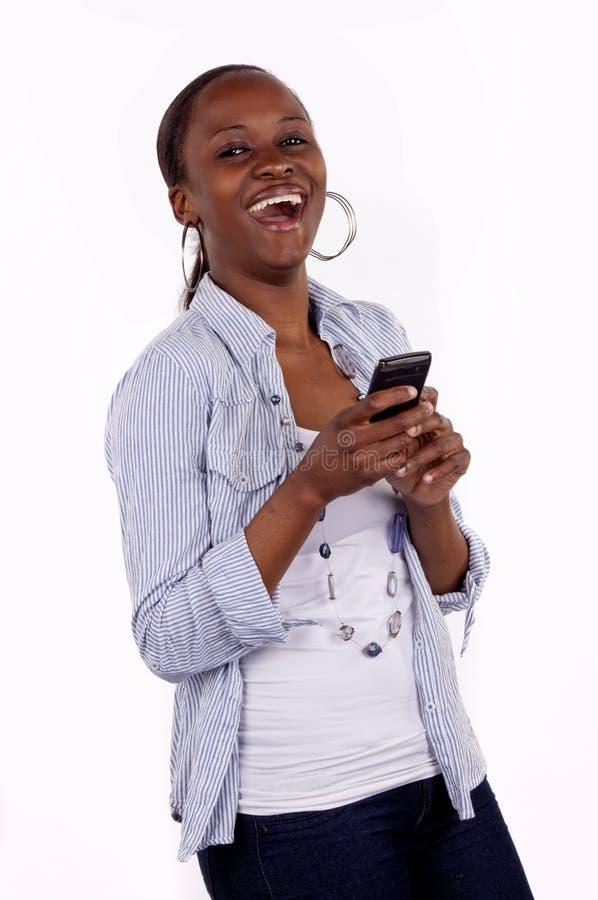 смеясь над sms texting женщина стоковые изображения