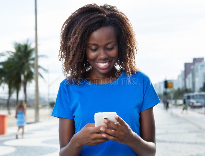 Смеясь над африканская женщина в голубой рубашке посылая сообщение с телефоном стоковая фотография