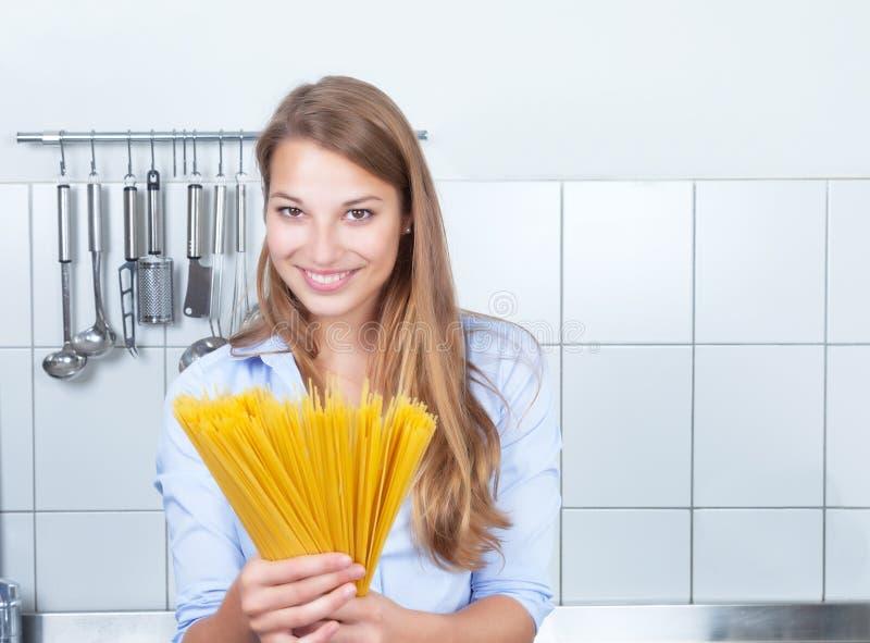 Смеясь над белокурая женщина с спагетти на кухне стоковые фото