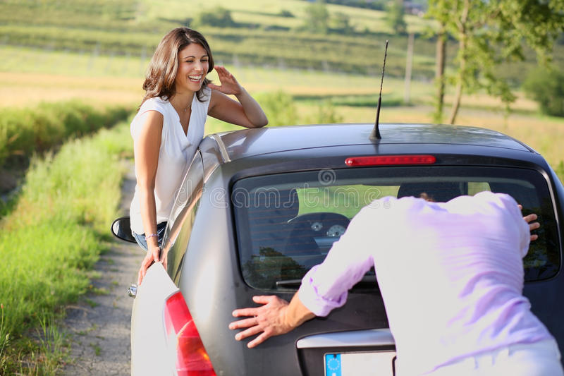 Смеясь над девушка и парень нажимая автомобиль стоковая фотография rf