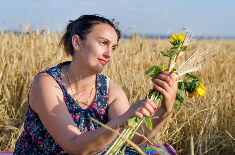 Смеясь над женщина держа цветки в пшеничном поле стоковые фотографии rf