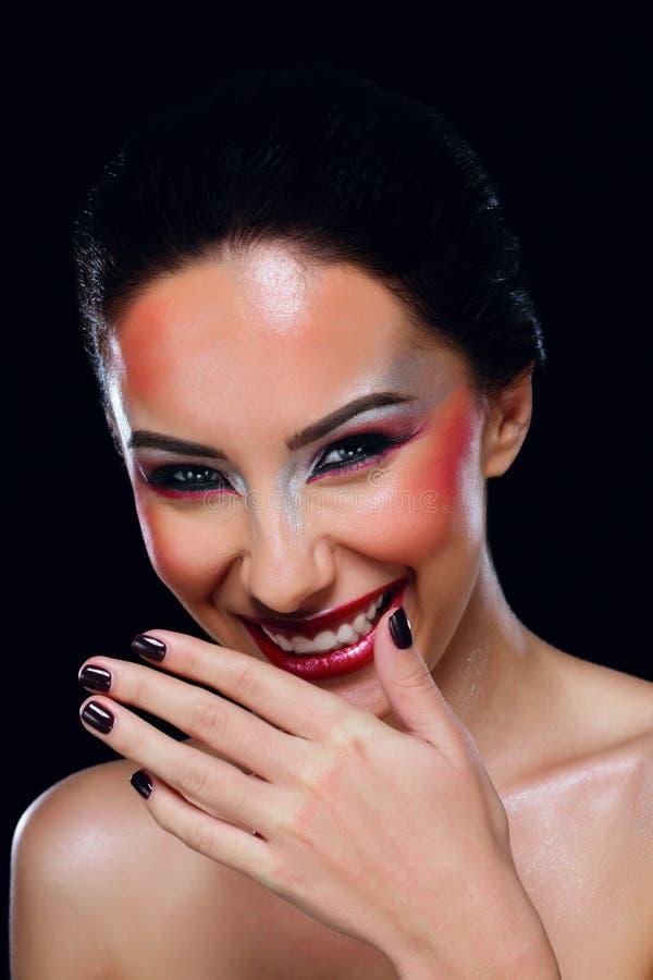 Смеясь над женщина покрывает ее рот вручную стоковые изображения rf