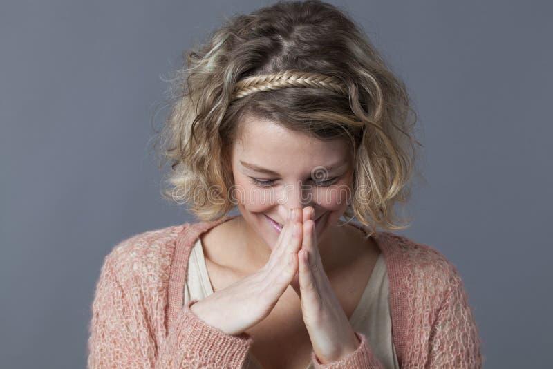 Смеясь над женщина 20s пряча ее улыбку и ободрение стоковая фотография