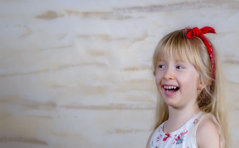 Смеясь над маленькая белокурая девушка с красным смычком стоковое фото rf