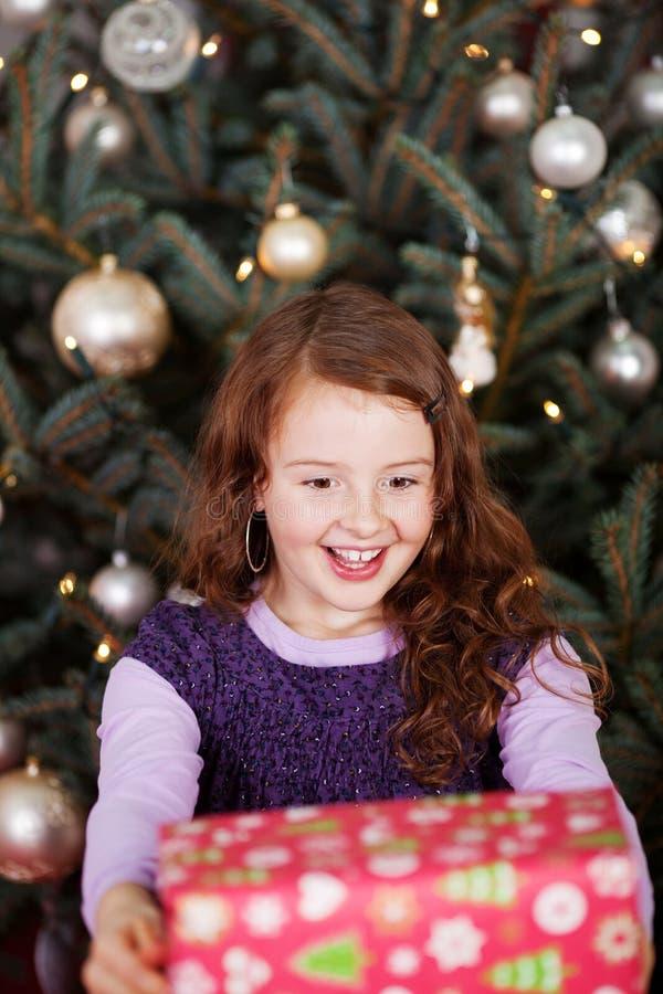 Смеясь над маленькая девочка держа подарок рождества стоковые фото