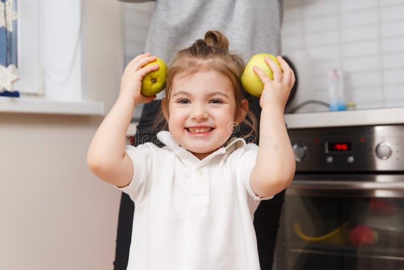 Смеясь над маленькая девочка с яблоками стоковые изображения