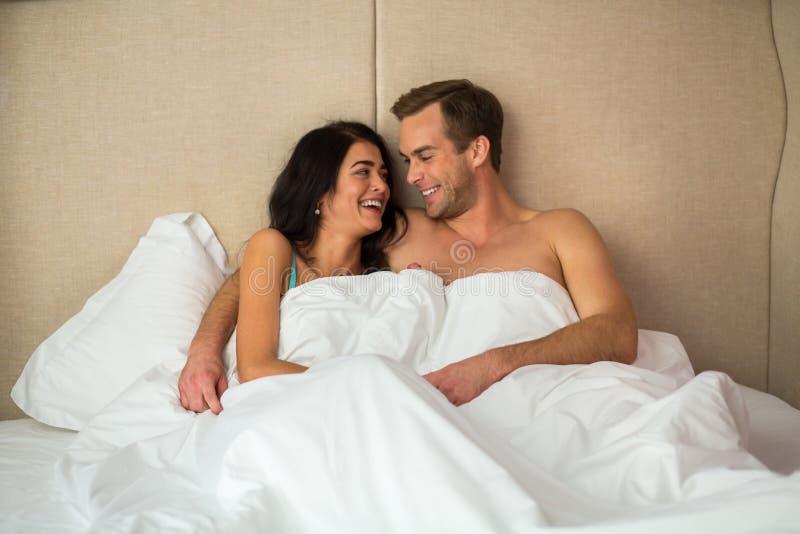 Смеясь над пары в кровати стоковое фото rf