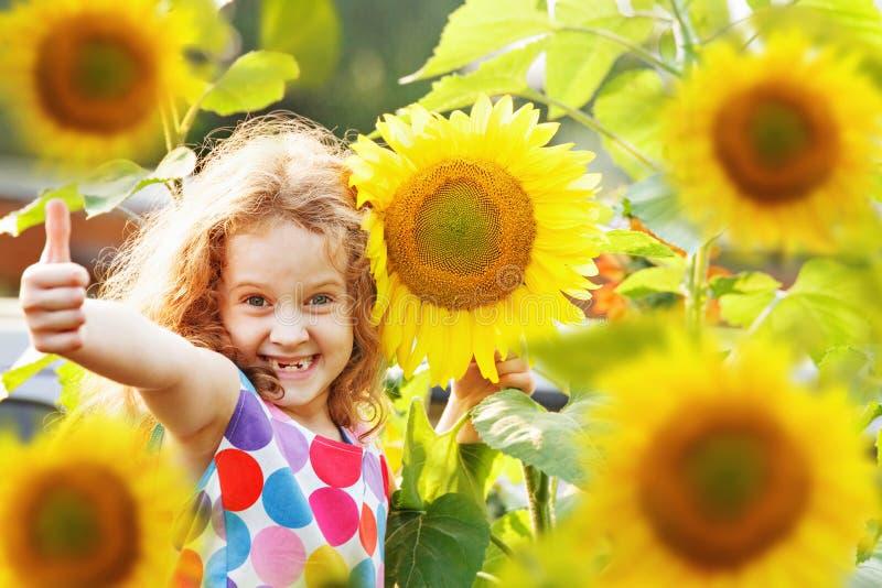 Смеясь над ребенок при солнцецвет, показывая большие пальцы руки вверх стоковое изображение rf