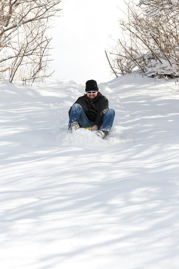 Смеясь над человек sledging в глубоком снеге, зиме концепции и ri саней стоковое изображение