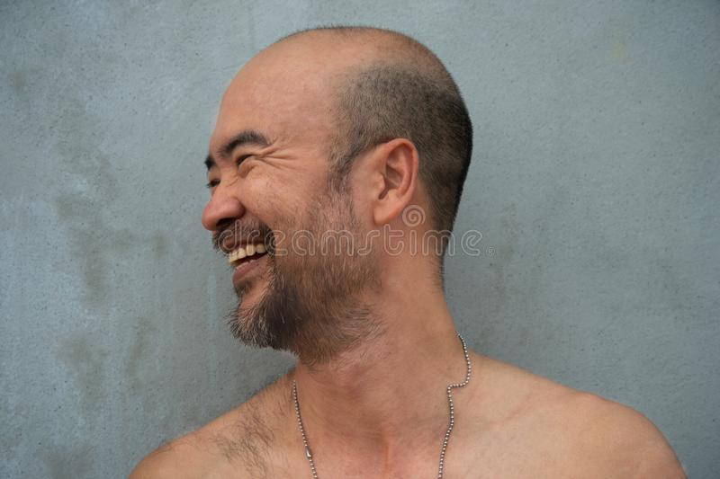 Смеясь профиль портрета человека бороды 30-40s лысого японского топлесс счастливого крутого на серой предпосылке бетонной стены стоковые фото