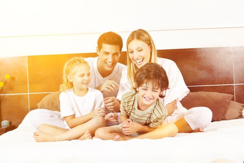 Смеясь семья сидит в кровати стоковые изображения
