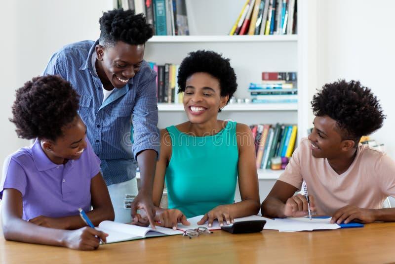 Смеясь студенты Афро-американского женского гувернера уча стоковое фото rf