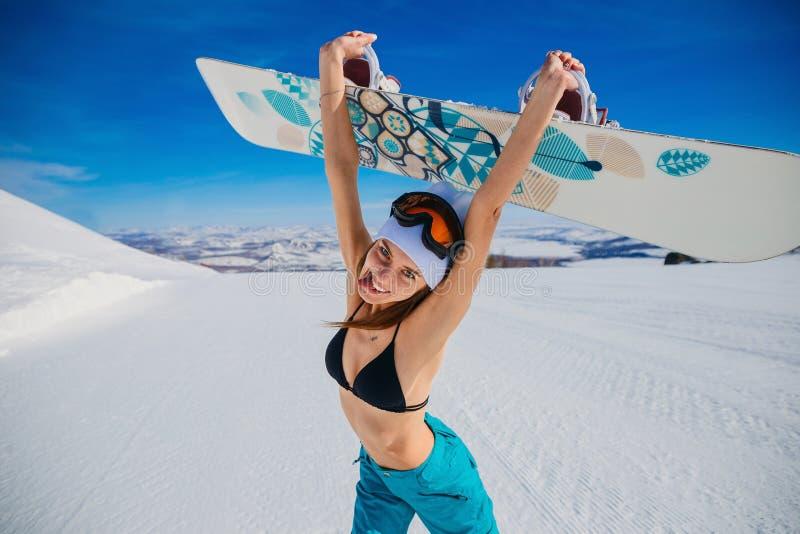 Смеясь эмоциональная молодая женщина в купальнике и шляпе держа сноуборд в ее руках в зиме весьма спорт эйфория Женщина стоковое фото